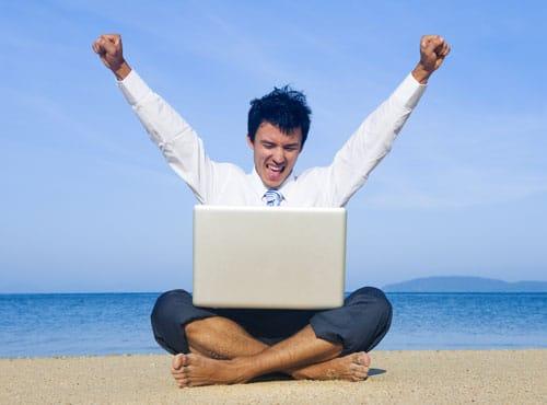 Image d'un homme heureux sur la plage en train de travailler