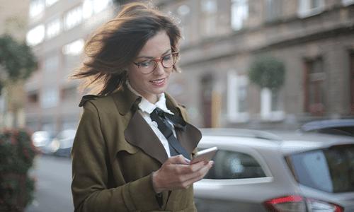 Image d'une femme sur son smartphone dehors